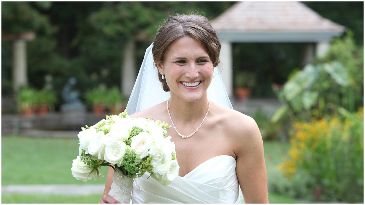 Woman smiling outside in her wedding dress
