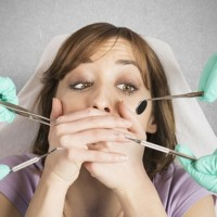 woman surrounded by dental instruments who's afraid