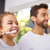 A father and daughter both brushing their teeth together